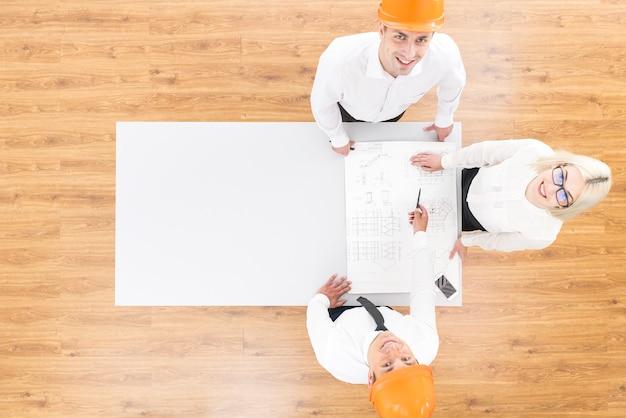 De drie ingenieurs werken met een blauwdruk op tafel. uitzicht van boven