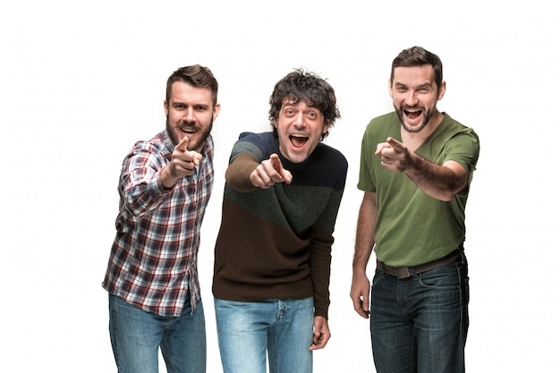 De drie mannen glimlachen, kijken en wijzen naar de camera