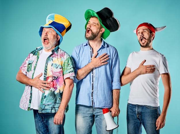 De drie voetbalfans zingen het volkslied over blauw