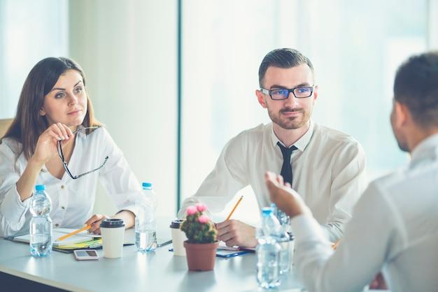 De drie zakenmensen zitten aan tafel en bespreken