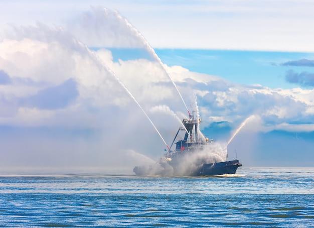 De drijvende sleepboot spuit waterstralen