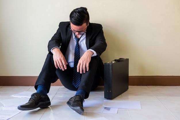 De droevige aziatische zakenman zit op vloer