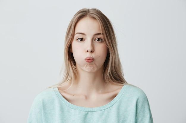 De droevige blonde jonge vrouw heeft knorrige uitdrukking pruilt haar lippen