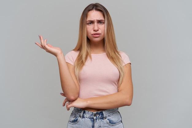 De droevige boos blonde jonge vrouw kijkt teleurgesteld en houdt lege ruimte op palm die over grijze muur wordt geïsoleerd