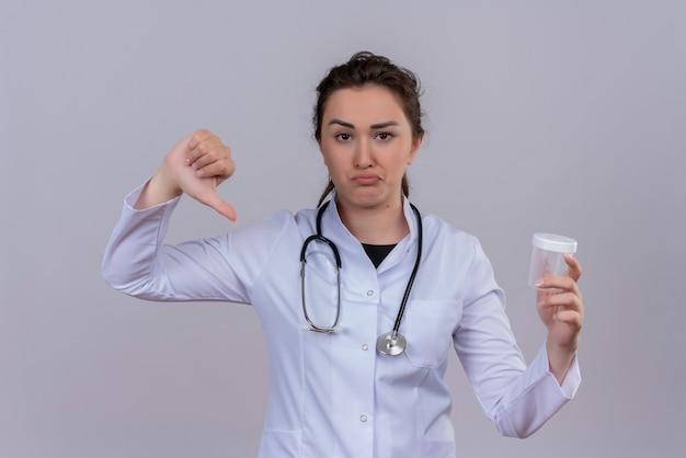 De droevige jonge arts die medische toga draagt die een lege stethoscoop draagt kan haar duim neer op witte muur