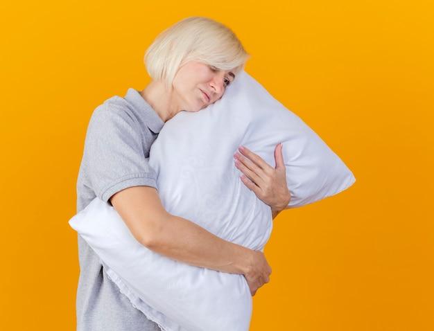 De droevige jonge blonde zieke vrouw koestert hoofdkussen die kant bekijken die op oranje muur wordt geïsoleerd