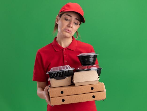 De droevige jonge mooie bezorger in uniform houdt papieren voedselpakketten en containers op pizzadozen die op groene muur worden geïsoleerd