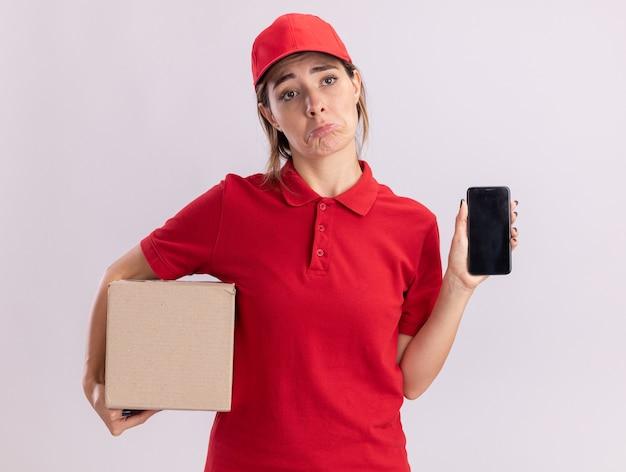De droevige jonge mooie leveringsvrouw in uniform houdt kartonnen doos en telefoon die op witte muur wordt geïsoleerd