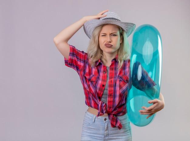 De droevige jonge vrouwelijke reiziger die rood overhemd draagt dat opblaasbare ring houdt, legt haar hand op hoed op geïsoleerde witte muur