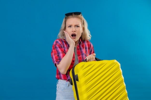De droevige jonge vrouwelijke reiziger die rood overhemd en een bril op de koffer van de hoofdholding draagt, legde haar hand op de wang op geïsoleerde blauwe muur