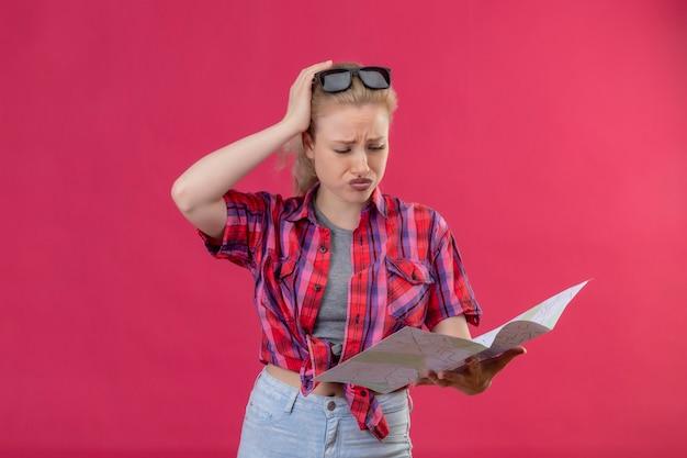 De droevige jonge vrouwelijke reiziger die rood overhemd en een bril op haar hoofd draagt die naar kaart kijkt, legde haar hand op het hoofd op geïsoleerde roze muur