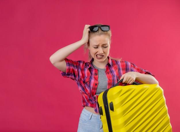 De droevige jonge vrouwelijke reiziger die rood overhemd in glazen draagt die koffer houdt, legde haar hand op het hoofd op geïsoleerde roze muur