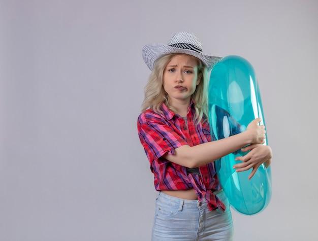 De droevige jonge vrouwelijke reiziger die rood overhemd in hoed draagt, omhelst opblaasbare ring op geïsoleerde witte muur