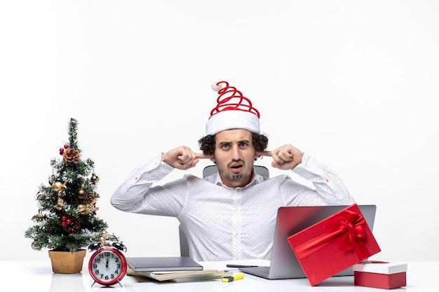 De droevige jonge zakenman die met grappige kerstmanhoed kerstmis viert en zijn oren sluit, verhindert het luisteren op kantoor op witte achtergrond