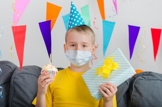 De droevige jongen in het gezichtsmasker van de geneeskunde met in hand giften viert verjaardag