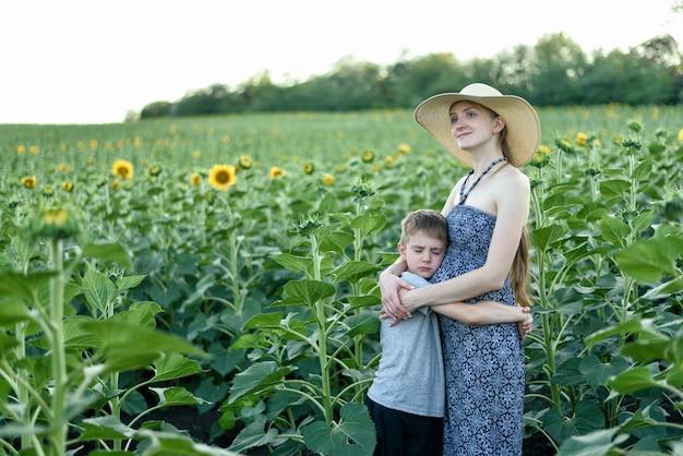 De droevige kleine zoon omhelst zwangere moeder die zich op een gebied van bloeiende zonnebloemen bevindt
