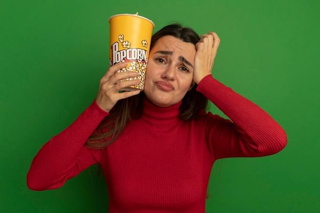 De droevige mooie vrouw houdt emmer popcorn vast en legt hand op hoofd dat op groene muur wordt geïsoleerd