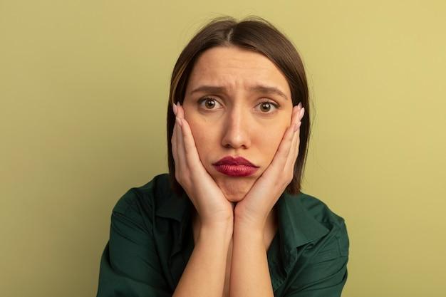 De droevige mooie vrouw legt handen op gezicht dat op olijfgroene muur wordt geïsoleerd