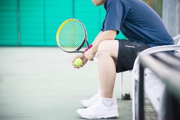 De droevige tennisspeler die in het hof zit na verliest een gelijke