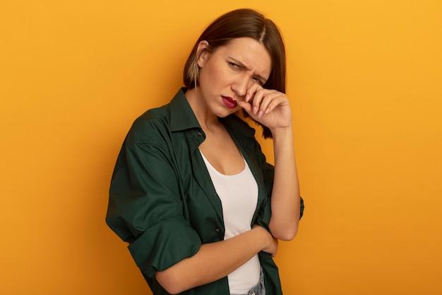 De droevige vrij kaukasische vrouw legt vinger op ooglid die kant op sinaasappel bekijkt