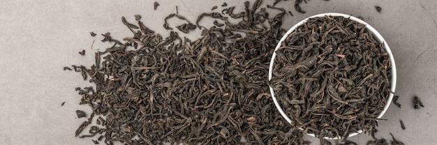 De droge thee wordt gegoten in een witte ceramische kop op een grijze geweven achtergrond. uitzicht van boven. lay-out.