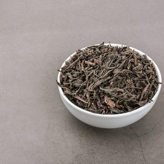 De droge thee wordt gegoten in een witte ceramische kop op een grijze geweven achtergrond.