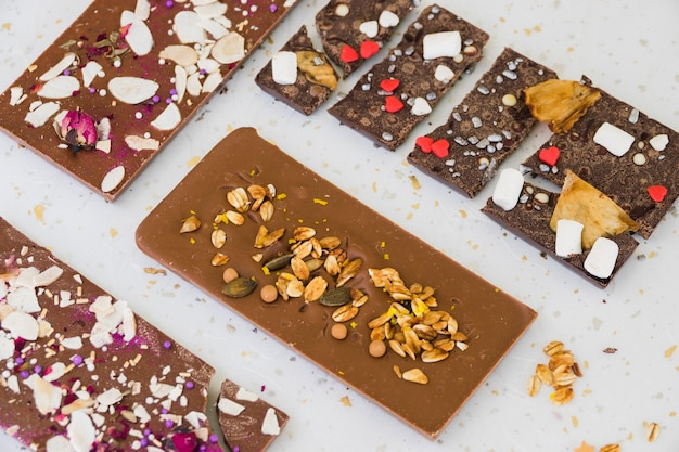 De droge vruchten en bestrooit op chocoladereep tegen witte achtergrond