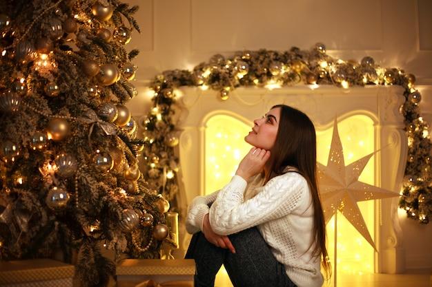 De dromerige vrouw dichtbij kerstboom met lichten het verfraaien en stelt voor
