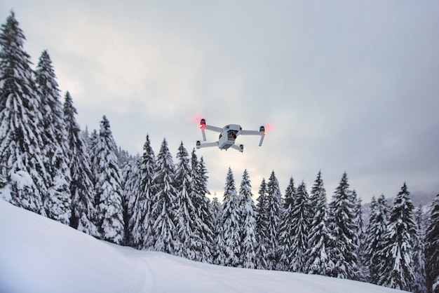 De drone is net opgestaan tijdens de vlucht na sneeuwval bij bomen
