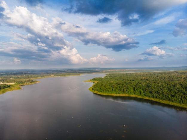 De drone schoot luchtmening toneellandschap een grote rivier met vers groen boombos en berg tegen een blauwe hemel