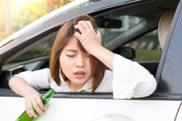 De dronken aziatische vrouw voelt duizelig na teveel het drinken van alcohol en het drijven van auto
