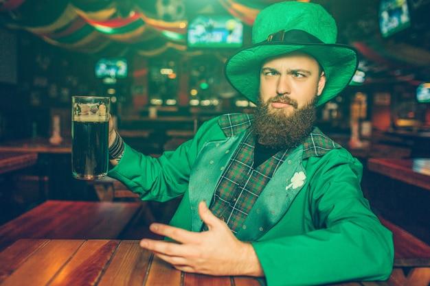 De dronken jonge mens in het kostuum van groene st. patrick zit aan lijst in bar. hij houdt een mok donker bier vast. kerel chillen.