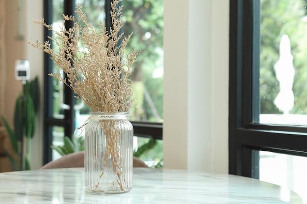 De droogbloemen in de vaas op tafel worden gebruikt om de coffeeshop te versieren.