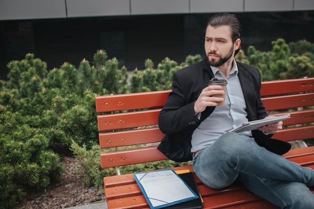 De drukke man heeft haast, hij heeft geen tijd, hij gaat buiten een snack eten. zakenman doet meerdere taken. multitasking zakenman.