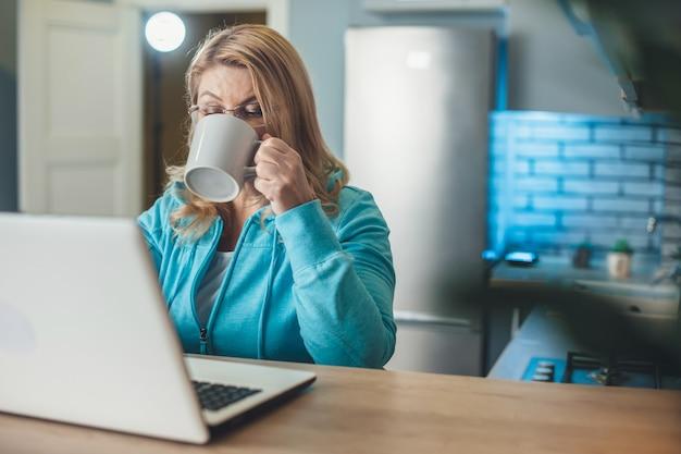 De drukke senior blonde vrouw drinkt een kopje thee tijdens het werken vanuit huis op de laptop in de keuken