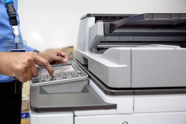 De drukknop van de zakenman die fotokopieerapparaat of printer gebruiken is de apparatuur van het het werkhulpmiddel van het bureau voor het scannen van document en kopieerpapier.