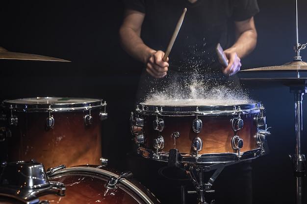 De drummer bespeelt de snaredrum met opspattend water.