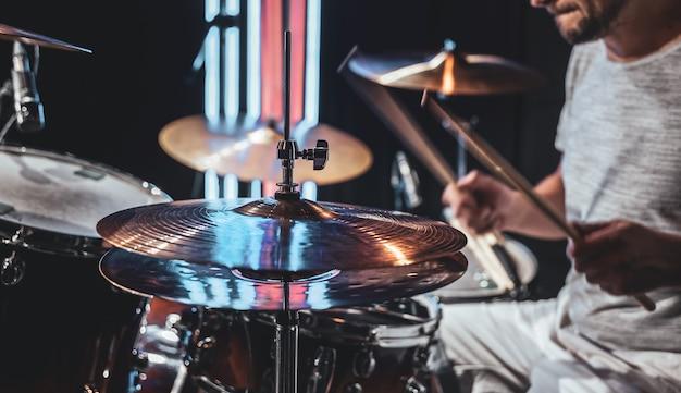 De drummer die stokken gebruikt tijdens het spelen op drums tijdens het optreden.