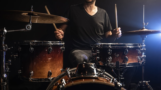 De drummer speelt drums terwijl hij aan het drumstel op het podium zit