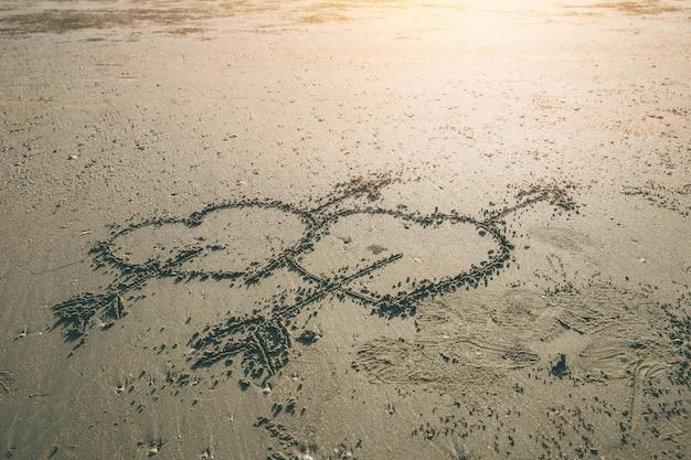 De dubbele pijl van het liefdehart van cupidosymbool trekt op het overzeese strand met zonsondergangachtergrond