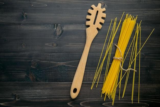 De dunne spaghetti op zwart hout