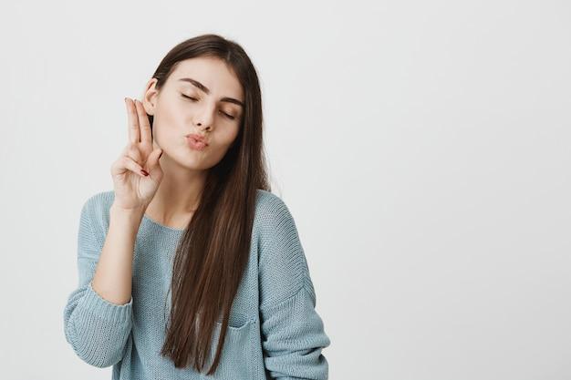 De dwaze leuke vrouw toont vredesteken en waait kus
