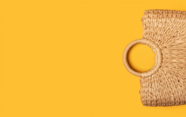 De ecozak van rieten stro of rotanvrouwen op gele muur. plat lag bovenaanzicht. concept van reizen zomer muur met kopie ruimte. strand accessoires