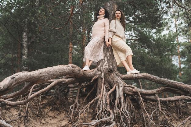 De eenheid van mens en natuur creatieve foto van twee zussen tussen de wortels van bomen een plek voor tekst...