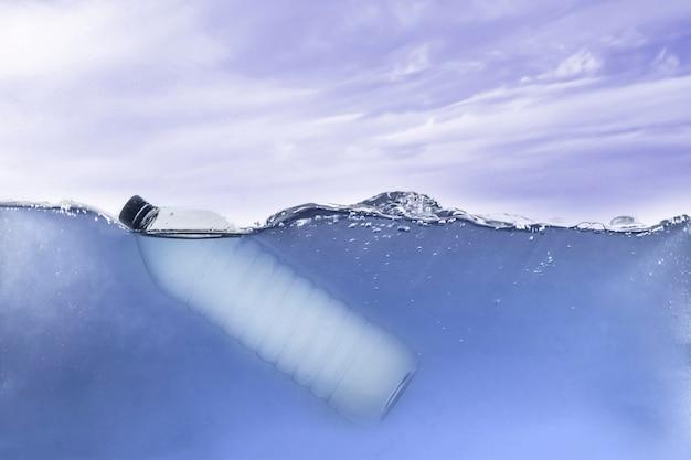 De eenvoudige enkele plastic fles in oceaanwater onder water, milieuproblemen en vervuiling