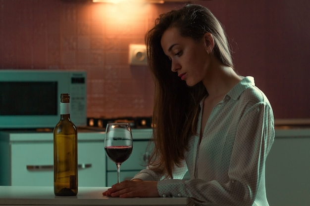De eenzame, droevige mooie jonge vrouw in een blouse met alcoholische drank drinkt alleen thuis in avond. vrouwelijk alcoholisme en alcoholverslaving