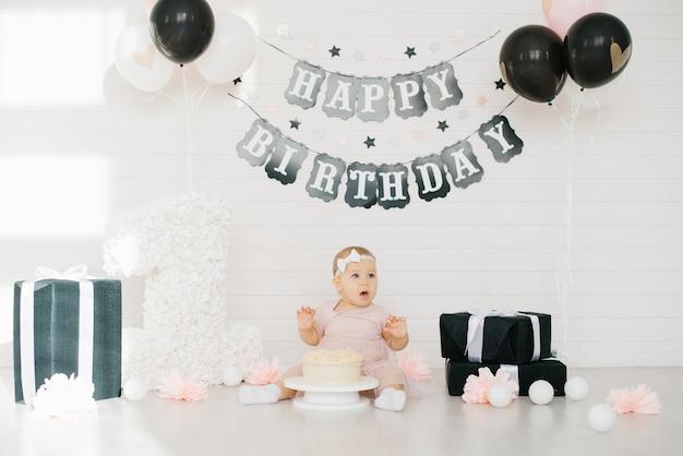 De eerste cake voor meisjes van één jaar. verjaardagsfeestdecoratie in zwart en wit. het kind proeft de zoetheid. gelukkige verjaardag