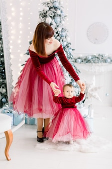 De eerste stappen van een schattig klein mooi meisje, met een vrij elegante moeder, die haar ondersteunt