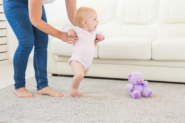 De eerste stappen van het babymeisje met de hulp van mamma