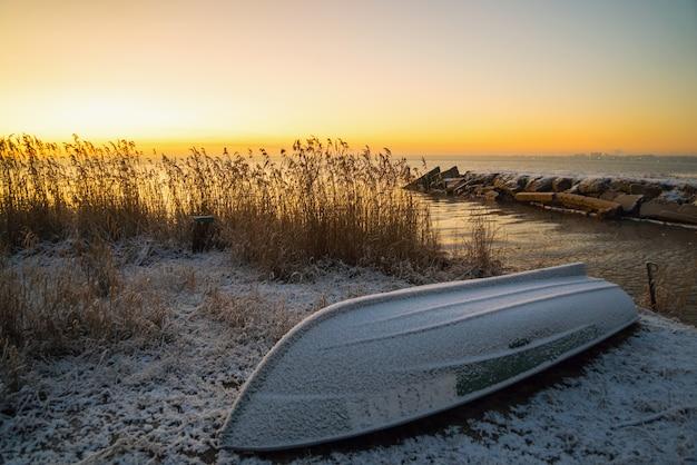 De eerste stralen van de zon over het ladogameer in de ochtend in de winter. een ten val gebrachte boot op een sneeuwstrand.